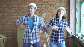 Радостные построители в шлемах танцуя во время ремонтов акции видеоматериалы