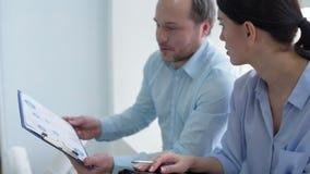 Радостные сотрудники обсуждая стратегии бизнеса в офисе акции видеоматериалы
