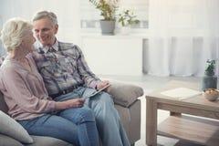 Радостные старшие пары отдыхая с прибором Стоковая Фотография RF