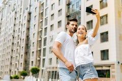 Радостные счастливые пары принимая selfies Стоковое Изображение RF