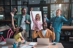 Радостные умелые коллеги празднуют их триумф Стоковые Изображения