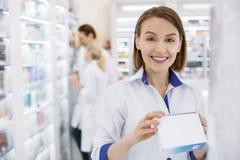 Радостный женский аптекарь принимая лекарство стоковое фото rf