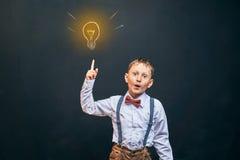Радостный мальчик, на черной предпосылке была идея и как символ шарик освещенный вверх ребенок кричит и указывает на стоковая фотография