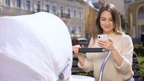 Радостный молодой форум интернета чтения матери на детской дорожной коляске смартфона отбрасывая сток-видео