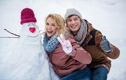 Радостный молодой человек и женщина имея потеху с снегом в зиме Стоковые Изображения
