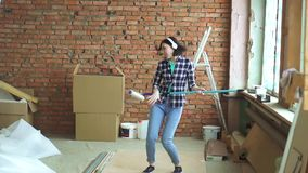 Радостный построитель девушки играет мнимую гитару во время ремонта сток-видео
