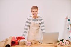 Радостный приятный мужской продавец работая с компьтер-книжкой в сувенирном магазине Стоковое Фото