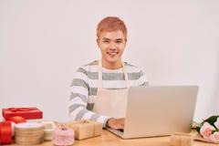 Радостный приятный мужской продавец работая с компьтер-книжкой в сувенирном магазине Стоковые Фотографии RF