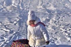 Радостный ребенок девушки взбирается вверх холм Она волочит трубопровод скелетона Девушка приниманнсяый за sledding на скольжения стоковое фото rf
