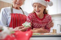 Радостный ребенок есть печенье испек ее бабушкой Стоковая Фотография RF