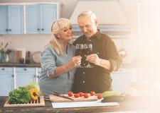 Радостный старшие супруг и жена празднуя годовщину в кухне Стоковая Фотография