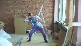 Радостный человек в рубашке шотландки с роликом краски имеет потеху и поет во время ремонтов акции видеоматериалы