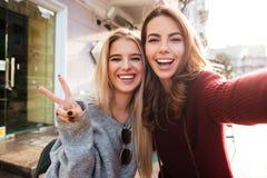 2 радостных привлекательных девушки принимая selfie пока сидящ совместно Стоковые Фото