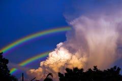 радуга появляется в небо после дождя и задней части на облаке захода солнца стоковые фото