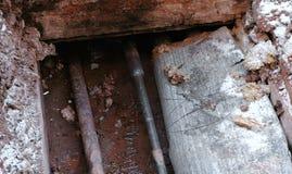 Разбейте, трубы взрыва и протекая вода под землей Выкопенные экскаватором трубы в зиме Стоковое Изображение