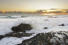 разбивая волны захода солнца Стоковые Изображения