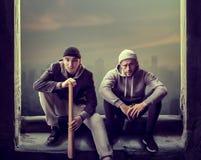 2 разбойника сидят на корточках перед окном стоковые фотографии rf