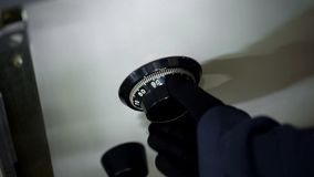 Разбойники вручают в черных перчатках открывая комбинацию на сейфе, шкале, конце вверх стоковое изображение rf