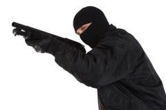 Разбойник в черной маске с корокоствольным оружием стоковая фотография