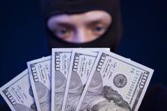 Разбойник держа деньги изолированный на синем стоковая фотография rf