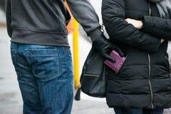 Разбойник крадя муфту от куртки женщины на улице Стоковое фото RF