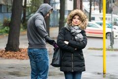 Разбойник крадя муфту от куртки женщины на улице Стоковое Изображение RF
