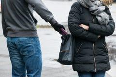 Разбойник крадя муфту от куртки женщины на улице Стоковые Изображения