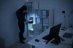 Разбойник при электрофонарь ища для документов в офисе Стоковые Фотографии RF