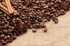 Разбрасывают зажаренные в духовке кофейные зерна на дерюгу с анисовкой звезды и ручками циннамона стоковая фотография rf