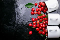 Разбросанная вишня от чашек эмали Вишни в железной чашке на черной предпосылке Здоровый, плодоовощ лета Вишни 3 Взгляд сверху Стоковые Фото