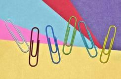 Разбросанные бумажные зажимы на красочной предпосылке стоковая фотография rf