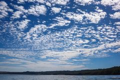 Разбросанные облака над голубым небом Стоковые Изображения