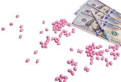 Разбросанные розовые пилюльки на белой предпосылке рядом с долларами США Стоковые Изображения RF