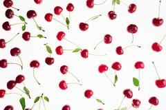 Разбросанные свежие зрелые вишни с кабелями, листьями на белой предпосылке Предпосылка вишни Стоковая Фотография RF