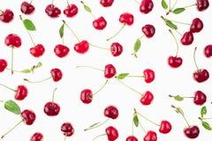 Разбросанные свежие зрелые вишни с кабелями, листьями на белой предпосылке Стоковое Изображение