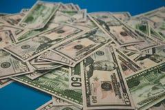 Разбросанный конец-вверх долларовых банкнот 50 долларов голубой предпосылки стоковая фотография rf