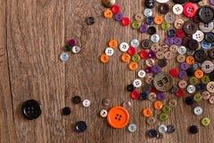 Разбросанный красочный шить застегивает на деревянной предпосылке Стоковое Фото
