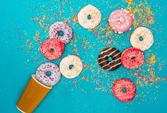Разбросал несколько donuts с различной поливой Donuts изолированные на голубой предпосылке Стоковая Фотография RF