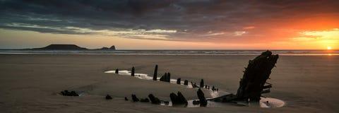 Развалина корабля панорамы ландшафта на пляже залива Rhosilli в Уэльсе на Стоковое Изображение