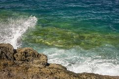 Развевайте ломать на утесе с океаном голубого зеленого цвета стоковое фото