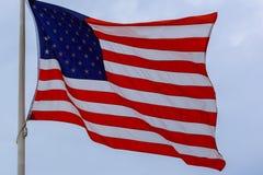 развевая американский флаг над голубым небом стоковые фото