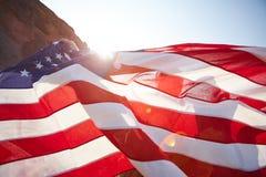 Развевая американское знамя в солнечном свете Стоковые Изображения