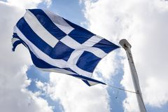 Развевая греческий флаг против голубого неба с облаками Стоковые Фотографии RF
