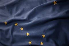 Развевая красочный флаг положения Аляски стоковые изображения rf