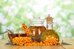 Разветвите с ягодами крушины моря, бутылки масла и чая на abst Стоковая Фотография