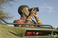Разведчик Masai с биноклями ищет животные от Landcruiser во время туристского привода игры на охране природы живой природы Lewa в Стоковое Изображение RF