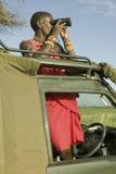 Разведчик Masai с биноклями ищет животные от Landcruiser во время туристского привода игры на охране природы живой природы Lewa в Стоковые Изображения