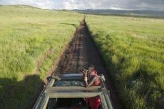 Разведчик Masai с биноклями ищет животные от Landcruiser во время туристского привода игры на охране природы живой природы Lewa в Стоковое Изображение