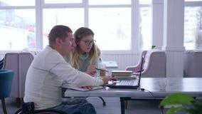 Развитие инвалидности, женщина учителя в eyeglasses проводит лекцию для инвалидного мужчины на кресло-коляске используя ноутбук видеоматериал