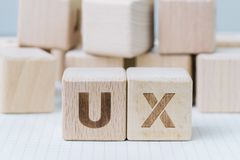 Развитие UX, идея проекта опыта потребителя, блок куба деревянный совмещая акроним UX на тетради gridline, потребителе центрально стоковое фото